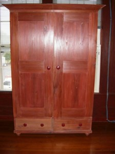 Pine Armoire with two sections for hanging clothes and two drawers at the bottom.